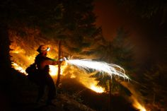 National Geographic Your Shot: A member of a hotshot firefighting crew firing a berry pistol to help ignite a night burnout in Oregon by Kyle Miller