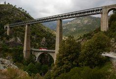 Corsica Frankrijk Spoorbrug van de architect Eiffel over de rivier Vecchio. Daaronder een boogbrug over een lokale weg.
