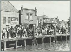 Mensen op de kade in Urk wachten op de aankomst van een boot in de haven 1934 #Urk