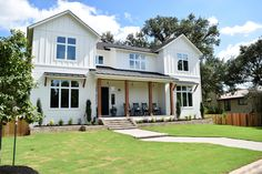 White modern farmhouse exterior. Benjamin Moore Simply White siding, black metal and shingle roof, cedar posts. Horizontal siding and board and batten. Front porch with rocking chairs.