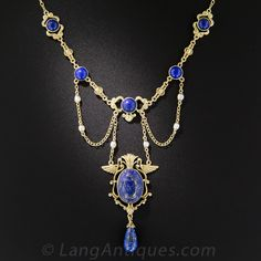 Egyptian Revival Lapis and Seed Pearl Necklace. This fabulous early-20th century find features a varied array of royal blue lapis lazuli gemstones, including a central hand carved scarab crowned with a watchful pair of birds (Ibises maybe?) with a handful of natural freshwater pearls added for a dash of luster. A rare, exotic, exciting and exceptional, original Egyptian Revival necklace measuring 15 1/2 inches.
