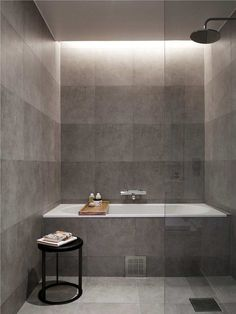 carry gray concrete tiles up along shower floor and tub | drop in white tub | faucets coming from wall | shower head and fixtures mounted on same wall as tub hardware (right wall) | glass panel | try to match walls w shower fixture to walls outside of wet room area | square drain