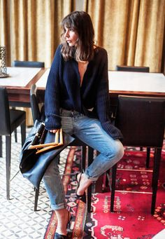 Blogger Irina Lakicevic wears a navy blue Stella McCartney buckle sweater with cuffed jeans, a black bag, and slingback pumps