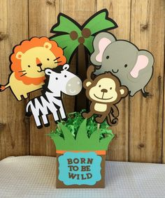 This centerpiece featuring four jungle animals can be used for either a birthday party or a baby shower. It comes with all four animals assembled and attached to a dowel. The centerpiece also includes a decorated paper box, foam cube, and paper shreds. Jungle Theme Birthday, Wild One Birthday Party, Safari Birthday Party, Animal Birthday, First Birthday Parties, Jungle Party, Safari Theme, Baby Shower Centerpieces, Baby Shower Decorations