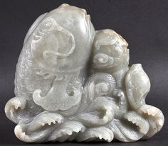 Description: A CHINESE QING DYNASTY CARVED GREEN JADE FIGURE OF A FISH the carp modelled emerging from crashing waves. 6.25ins x 5.75ins.