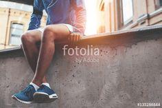"""Laden Sie das lizenzfreie Foto """"Male athlete in blue running shoes sitting and resting after street workout session at sunset"""" von mooshny zum günstigen Preis auf Fotolia.com herunter. Stöbern Sie in unserer Bilddatenbank und finden Sie schnell das perfekte Stockfoto für Ihr Marketing-Projekt!"""