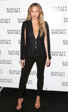 Chrissy Teigen wearing a black cape jacket with black trousers and ankle strap heels at the Badgley Mischka F/W 15 show // NYFW