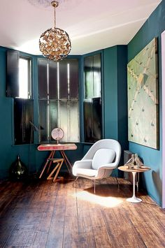 Teal reading nook with modern armchair and gold chandelier