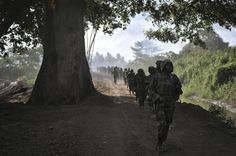 """Troops walk along the perimeter of Janaale, a town 94 km from Mogadishu, during an advance on 14 February. Ugandan troops, as part of the African Union Mission in Somalia (AMISOM), advanced with troops from the Somali National Army (SNA) on three towns in the Lower Shabelle region of Somalia in an operation codenamed """"Boot on the Ground"""" on 14 February.  AU UN IST PHOTO / TOBIN JONES"""