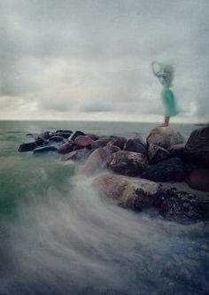 Girl in blue on rocky shore.