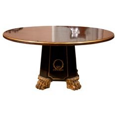 A  REGENCY INSPIRED CENTER TABLE  OF MACASSAR EBONY VENEERS WITH GILT EDGE TO TOP, CARVED  GILT PAW  FEET AND GILT  WREATH ON PEDESTAL.INLAID BRASS RING ON TOP