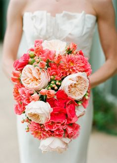Captivate with coral! A cascading bouquet of vibrant dahlias is perfectly punctuated with blush garden roses.