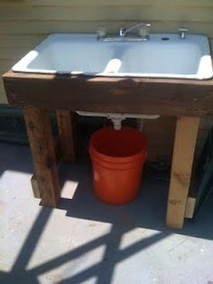 DIY: Outdoor sink.  Instead of the bucket, use PVC connectors and pipe to run grey water to the flowerbeds.  Secure a sprayer hose attachment for the veggies!