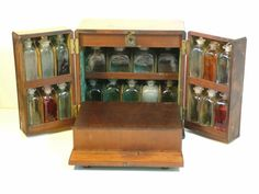 Antique Apothecary/Medical  Box c. 1800. UK. Two measuring jugs, one with its original leather case by S. Mawson & Thompson, London. Two zinc containers, glass stirring stick, glass pestle & mortar, four tin hinged boxes, brass & iron scales with its weights and one or two other glass bottles. (via Art & Antiques Online. CINOA)