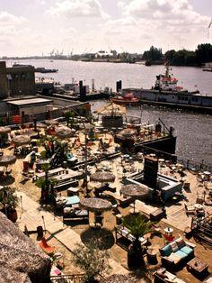 """Der """"Strand Pauli""""im Tiki-Style liegtdirekt an der Elbe und bietet einen einzigartigen Blick auf den Hamburger Hafen.Während man sich also ein kühles Astra und einen hausgemachten Burger gönnt, kann man entspannt den Schiffen hinterher schauen."""