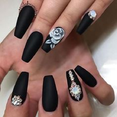 Elegant looking rose nail art design. The matte black background helps make the white rose on top stand out as well as makes the embellishments added be more noticeable.