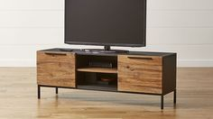 The ultimate in storage versatility, this multi-purpose small TV stand is rich with the texture of rustic teak, framed in matte black teak for a contemporary look. Paired with a black tubular steel base, the TV console offers combined open and concealed storage with two doors, three shelves and plenty of cord management.