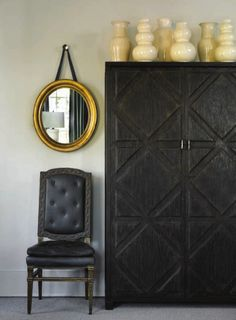 Black armoire with cream vases and black chair and gold oval mirror.