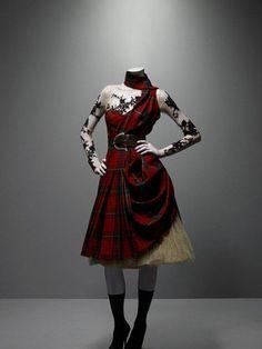 Alexander McQueen (British, 1969-2010). Ensemble Widows of Culloden , autumn / winter 2006-7. Dress of McQueen wool tartan; nude silk top of net appliquéd with black lace; cream silk underskirt of tulle
