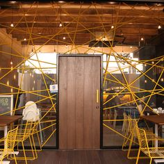 outofstock have based their design on a nest, using a steel frame covered with braided yellow rope which criss-cross the outer windows, holding the glass in place...