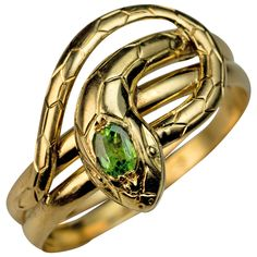 Antique Demantoid Gold Snake Ring. French, circa 1910  The 18K gold ring is finely modeled as a stylized coiled snake.   The head of the snake is embellished with a sparkling Russian demantoid.  The ring is marked with French eagle-shaped assay mark for 18K gold and maker's mark.