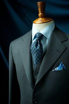 Dark grey suit, light blue shirt, navy tie with light blue medallions
