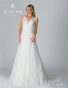 Style 527 Raven - Elegant soft tulle A-line bridal gown with Alcon lace and allover lace. Illusion bateau neckline with hand-beaded lace appliqués on allover lace, scalloped V neckline details, satin belt with mini bow, illusion back with misty tulle and satin covered buttons, court length train