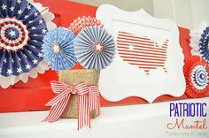 Add some Americana to your mantel with pinwheels, ribbon, and a framed flag.