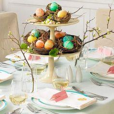 Pequenos ninhos seguram ovos coloridos e customizados - para combinar, cores claras na mesa e dois galhos, um de cada lado