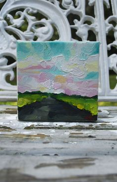 """""""The Greener place"""" by Emily Jeffords  a 4x4 inch oil painting on gallery wrapped canvas. This little guy is covered in lush, thick, impasto paint, in the dearest of shades: teal, green, and pink. I love the dark/light contrast, as well as the texture and depth in the sky."""