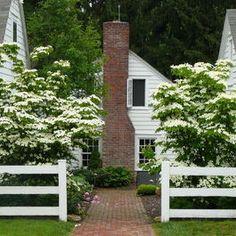 white farmhouse exterior with brick path & fireplace