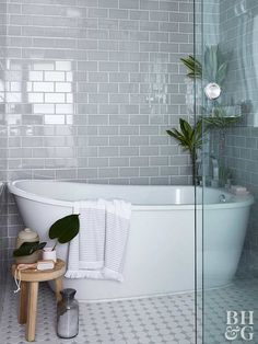 The master bath uses gray subway tile and gray-and-white mosaics to create a dynamic space. The deep tub and tropical plants make the bath area feel like a luxury spa. Glass panels give the sense of privacy without blocking natural light. White Subway Tile Bathroom, Grey Subway Tiles, Bathroom Floor Tiles, Modern Bathroom, Bathroom Ideas, Grey Tile Shower, Shower Ideas, Glass Tile Bathroom, Black Bathrooms