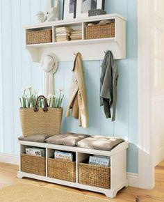 lambris mural en bois peint en bleu pastel dans l'entrée aménagée avec un banc et une étagère avec des paniers tressés
