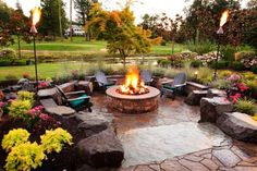 Gorgeous and carefully designed landscaping surrounds this fire pit patio area, creating an outdoor retreat for entertaining and relaxing. Classic Adirondack chairs provide ample seating for guests.