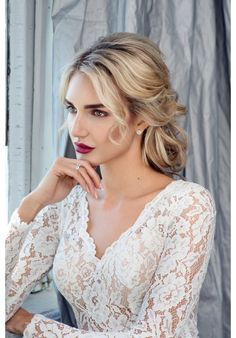 The epitome of elegance and class, this A-line dress features a long-sleeved top delicately constructed with lace and chiffon. A luxurious satin skirt adds a touch of class to this absolutely sensuous gown.