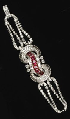 An Art Deco platinum, diamond and ruby bracelet, French, circa 1935. Set with rubies and diamonds in platinum. Centred with eight graduated oval-shaped rubies, and set with graduated circular and baguette-shaped diamonds overall.