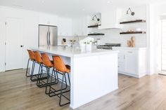 Modern Farmhouse interior design by Lindye Galloway Design. White kitchen, white shaker cabinets, white marble backsplash, wood panel island, open shelving, brass hardware, swing arm sconces and leather barstools.