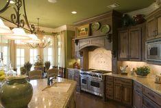 Medium brown cabinets, beige backsplash, and green walls.