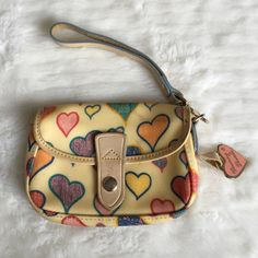 "Authentic Dooney & Bourke Hearts Wristlet 6x4"" Preowned Authentic Dooney & Bourke Hearts Wristlet 6x4"". Has signs of normal wear and is in very good condition. Please look at pictures for better reference. Happy shopping!  Dooney & Bourke Bags Clutches & Wristlets"