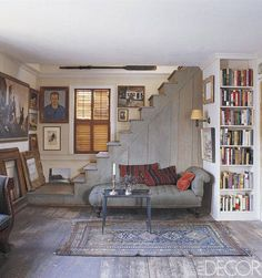 Painter John Dowd displays selections from his art collection in the stairwell of the 1820s cottage he restored in Provincetown, Massachusetts. A 1950s portrait by Judith Shahn of a local gas-station attendant hangs near a painting by Ross Moffett of chimney repairmen. The chaise longue is 19th century, and the wide plank floors are original to the house. - ELLEDecor.com