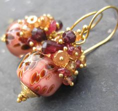 Swirling apricot, cream and pomegranate come together in the Creme Brulee boro lampwork bead earrings with padparadscha sapphire, citrine, and garnet. Amazing, handmade borosilicate lampwork beads are topped with a swirl of sunset-hued padparadscha sapphire briolettes and faceted garnet briolettes, as well as golden apricot quartz and sparkling citrine rondelles. This shimmering confection is poised on gold vermeil headpins and dangles from gold vermeil earwires. The Creme Brulee earrin...