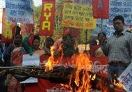 Protesters burn an effigy of Prime Minister Manmohan Singh at a protest rally.The body of a gang-rape victim was being flown back to New Delhi on Sunday after her death triggered a mass outpouring of grief and anger in India. Raped and savaged by six attackers who offered her and a male friend a ride home in a private bus on Dec. 16, the young physical therapy student was beaten and impaled with an iron rod for nearly an hour as the curtained bus floated through the city.