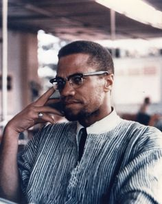 An ethnic African shirt thrown over a shirt with a tie plus browliners and Malcolm X make this picture a cool one