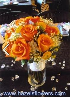 Bright Orange roses, & Light Blue Delphinium & yellow button poms accented with the softness of Baby's Breath makes this bouquet sing!