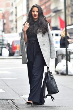 Olivia Munn adds interest to her all black look with a classic grey wool coat draped over her shoulders and a dark lip