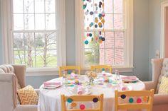 mesa posta para carnaval com confetes tamanho gigante decorado centro da mesa, cadeiras e lustre suspenso.