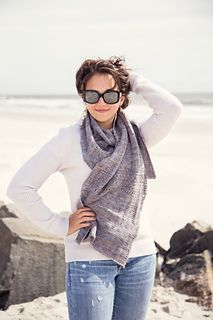 This scarf is worked with two strands of lace-weight yarn held together and features lace panels that run horizontally across the body.