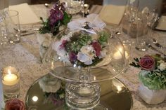 Glass Bell jars over posies of fresh flowers surrounded by posies and floating candles