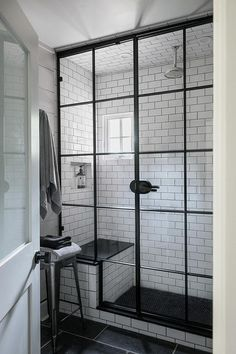 Freshen up in this gorgeous industrial bathroom featuring a Tolix stool positioned on black floor tiles leading to an industrial shower fitted with a white subway tiled surround contrasted with black grout and a built in tiled shower bench with a black seat while a rain shower head hangs over a black tiled floor.