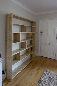Large reclaimed wooden bookcase with vertical dividers.